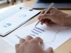 Imagem de mão de gestor com caneta e papel com gráficos e indicadores de resultados